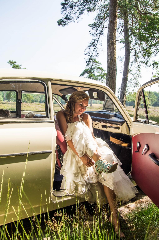 Bruid in de trouwauto midden in het bos